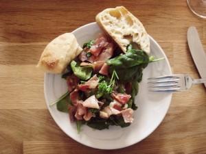 Eine köstliche Vorspeise aus Spinat als Salat mit Schinken und Mozzarella