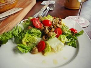 Der Salat zur Tortilla mit Oliven, Tomaten und einem Sherryessig-Öl-Dressing
